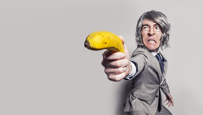 Un uomo con una banana in mano a mo di pistola