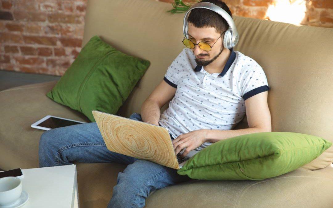 Un uomo mentre lavora sul divano con PC e cuffie
